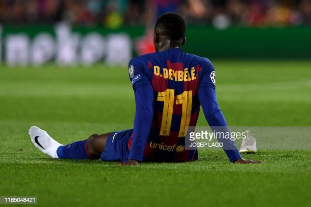 Barcelona's French forward Ousmane Dembele sits on the ground after an injury during the UEFA Champions League Group F football match between FC...