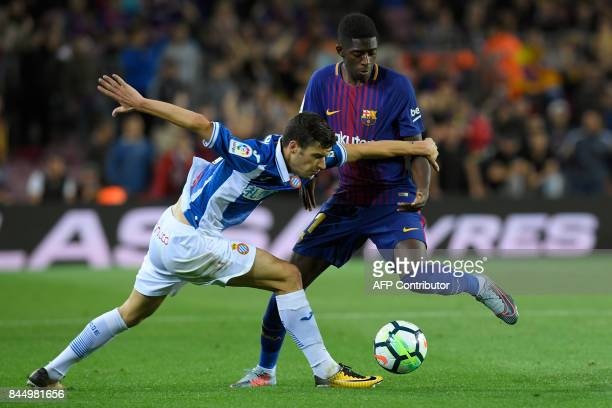 Barcelona's French forward Ousmane Dembele vies for the ball with Espanyol's defender Aron Martin during the Spanish Liga football match Barcelona vs...
