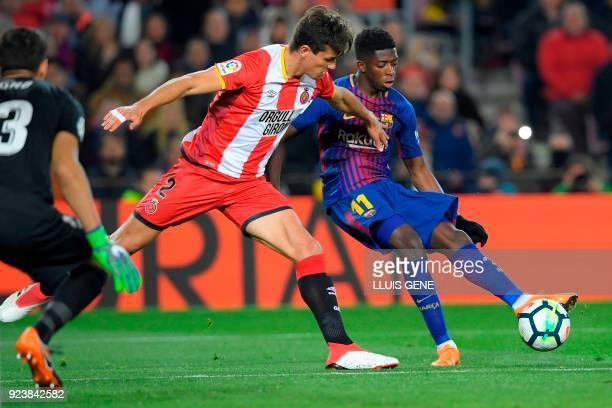 Barcelona's French forward Ousmane Dembele vies with Girona's Colombian defender Bernardo Espinosa and Girona's Moroccan goalkeeper Yassine Bounou...