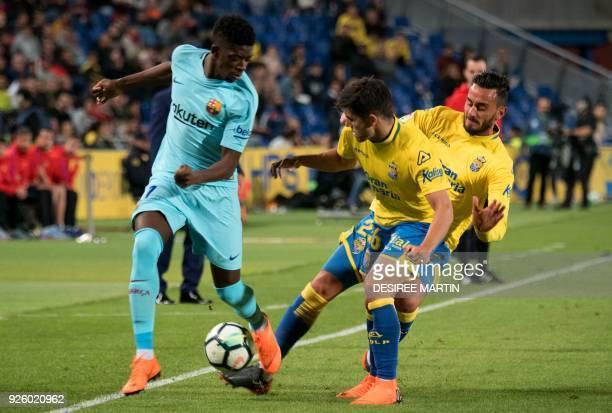 Barcelona's French midfielder Ousmane Dembele vies with Las Palmas' defender Aythami Artiles and Las Palmas' forward Asdrubal Padron during the...