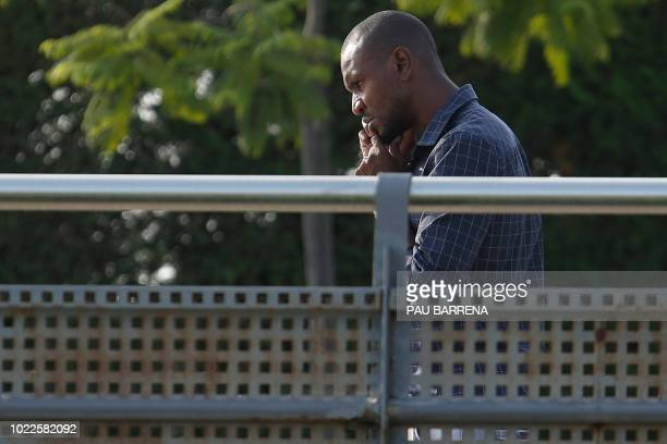 Barcelona's French technical secretary Eric Abidal uses his mobile as he arrives to attend a training session at the FC Barcelona's Joan Gamper...