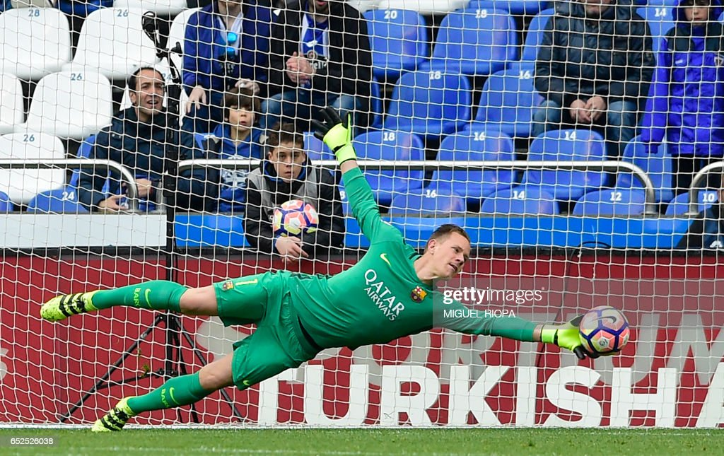 TOPSHOT - Barcelona's German goalkeeper Marc-Andre Ter Stegen dives to stop a ball during the Spanish league footbal match RC Deportivo de la Coruna vs FC Barcelona at the Municipal de Riazor stadium in La Coruna on March 12, 2017. /