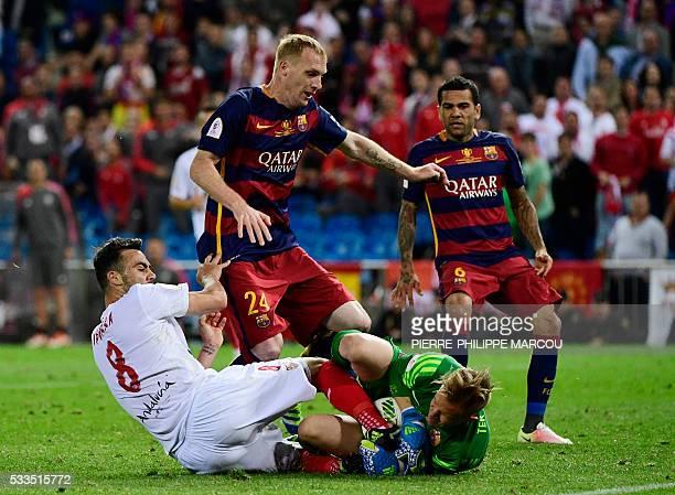 Barcelona's German goalkeeper MarcAndre Ter Stegen secures the ball next to Barcelona's French defender Jeremy Mathieu and Sevilla's midfielder...