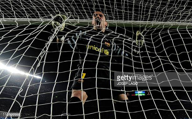Barcelona's goalkeeper Victor Valdes celebrates a goal by his teammate Barcelona's Argentinian forward Lionel Messi during their Champions League...