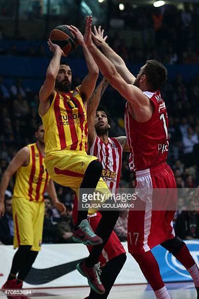 Barcelona's guard Juan Carlos Navarro tries to score past Olympiacos Piraeus' guard Evangelos Mantzaris during their play off Euroleague basketball...