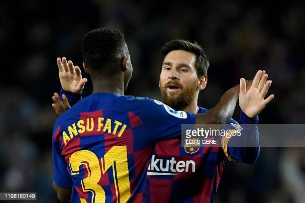 Barcelona's Guinea-Bissau forward Ansu Fati celebrates with Barcelona's Argentine forward Lionel Messi after scoring during the Spanish league...