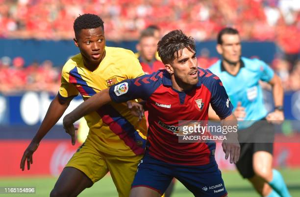 Barcelona´s GuineaBissau forward Ansu Fati challenges Osasuna's Spanish defender Nacho Vidal during the Spanish league football match CA Osasuna...