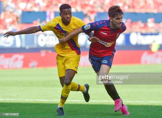 Barcelona´s GuineaBissau forward Ansu Fati challenges Osasuna's Spanish defender Nacho Vidal during the Spanish league football match CA Osasuna...