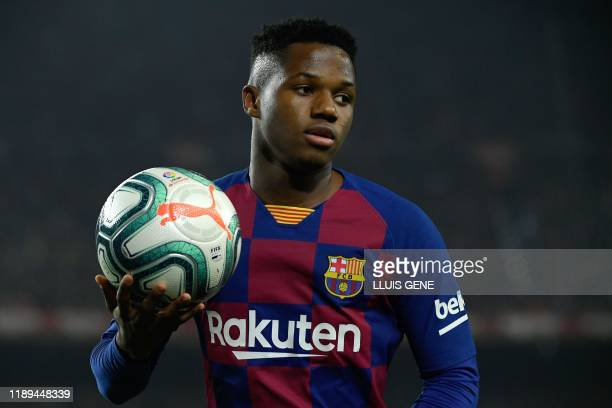 Barcelona's GuineaBissau forward Ansu Fati grabs the ball during the El Clasico Spanish League football match between Barcelona FC and Real Madrid CF...