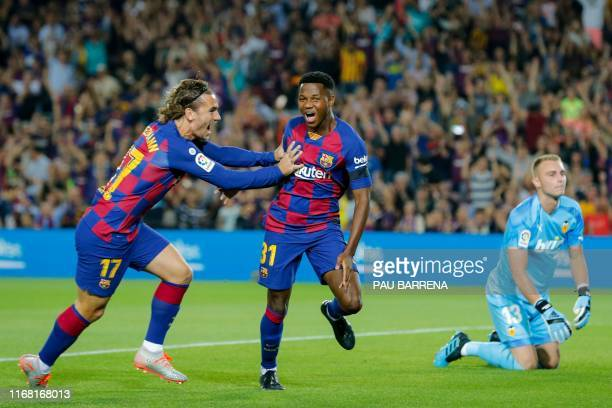 Barcelona´s Guinea-Bissau forward Ansu Fati is congratulated by Barcelona's French forward Antoine Griezmann after scoring a goal during the Spanish...