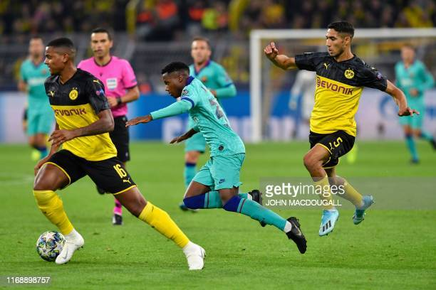 Barcelona´s GuineaBissau forward Ansu Fati is fouled by Dortmund's Moroccan defender Achraf Hakimi during the UEFA Champions League Group F football...