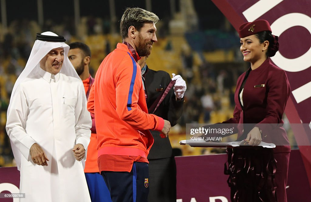 FC Barcelona's Lionel Messi receives a medal following a friendly football match between FC Barcelona and Saudi Arabia's Al-Ahli FC on December 13, 2016 in the Qatari capital Doha. Goals from Luiz Suarez, Lionel Messi and Neymar helped Barcelona beat Saudi champions Al-Ahli 5-3 in a thrilling friendly in Doha. The superstar trio all scored by the 17th minute, helping the Spanish giants to stroll into an early three-goal lead. JAAFAR