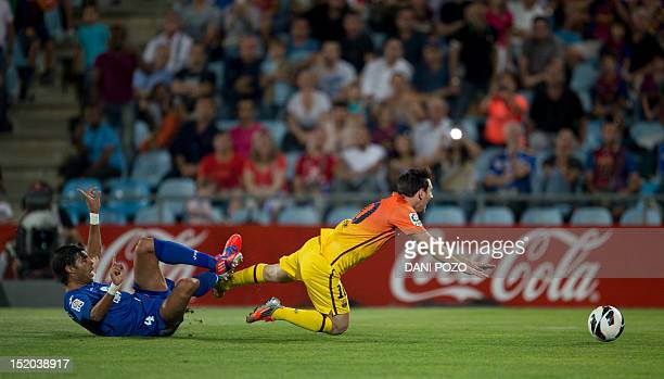 Barcelona's Lionel Messi vies for the ball with Getafe's Miguel Torres during the Spanish league football match between Getafe and Barcelona at the...