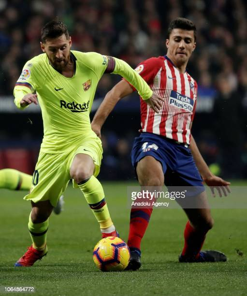 Barcelona's Lionel Messi vies with Rodri of Atletico Madrid during the La Liga football match between Atletico Madrid and FC Barcelona at the Wanda...