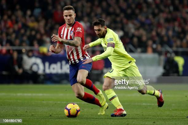 Barcelona's Lionel Messi vies with Saul Niguez of Atletico Madrid during the La Liga football match between Atletico Madrid and FC Barcelona at the...