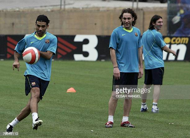 Barcelona's Mexican Rafael Marquez Argentinian Diego Milito and Leo Messi take part in a training session at the Camp Nou Stadium in Barcelona 07...
