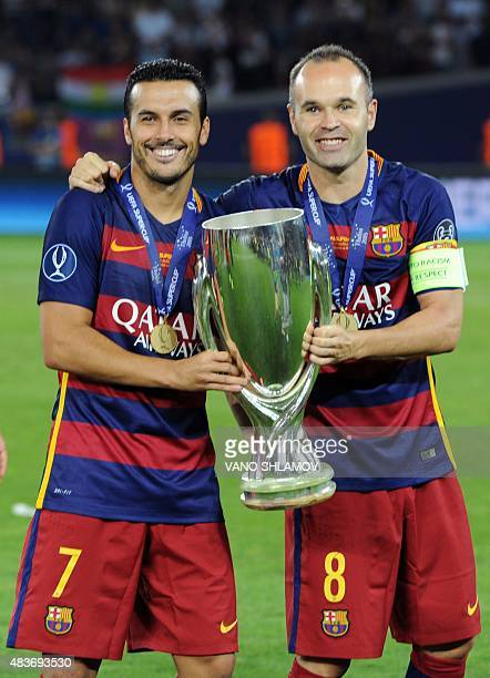 Barcelona's midfielder Andres Iniesta and Barcelona's forward Pedro Rodriguez celebrate with the trophy after winning the UEFA Super Cup final...