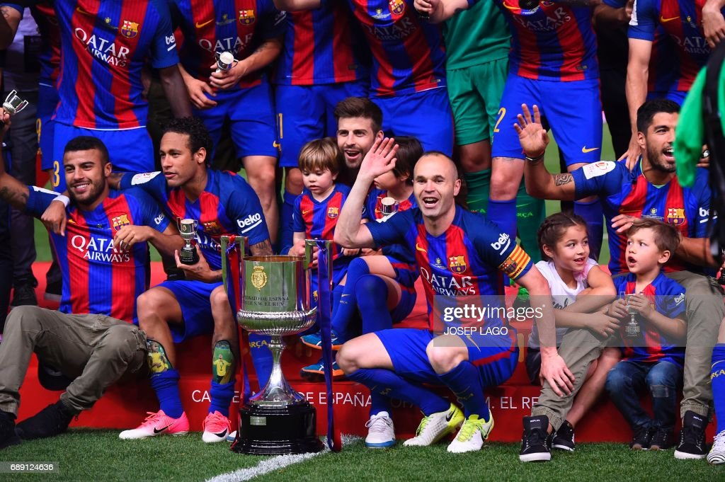 Barcelona's midfielder Andres Iniesta (C) and teammates celebrate their victory past the trophy after the team won the Spanish Copa del Rey (King's Cup) final football match FC Barcelona vs Deportivo Alaves at the Vicente Calderon stadium in Madrid on May 27, 2017. Barcelona won 3-1. / AFP PHOTO / Josep LAGO