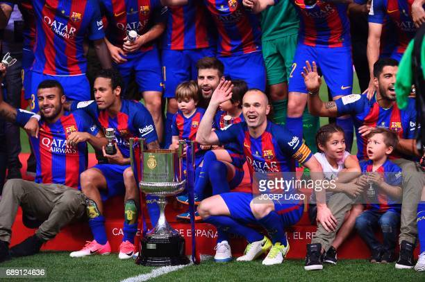 Barcelona's midfielder Andres Iniesta and teammates celebrate their victory past the trophy after the team won the Spanish Copa del Rey final...