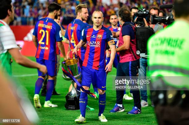Barcelona's midfielder Andres Iniesta carries the cup after the team won the Spanish Copa del Rey final football match FC Barcelona vs Deportivo...