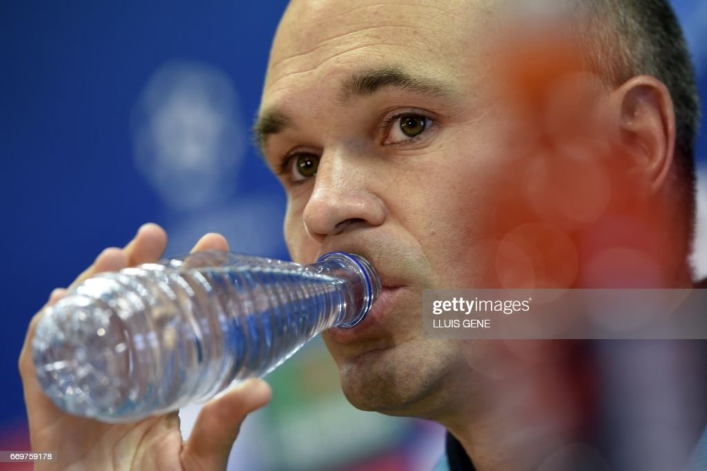 Barcelona's midfielder Andres Iniesta drinks during a press conference at the Joan Gamper Sports Center in Sant Joan Despi, near Barcelona, on April 18, 2017 on the eve of the UEFA Champions League quarter-final second leg football match FC Barcelona vs Juventus. /