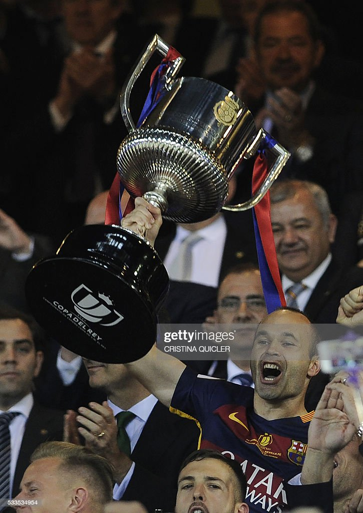 Barcelona's midfielder Andres Iniesta (C) holds the cup as he celebrates with teammates after winning the Spanish 'Copa del Rey' (King's Cup) final match FC Barcelona vs Sevilla FC at the Vicente Calderon stadium in Madrid on May 22, 2016. / AFP / CRISTINA
