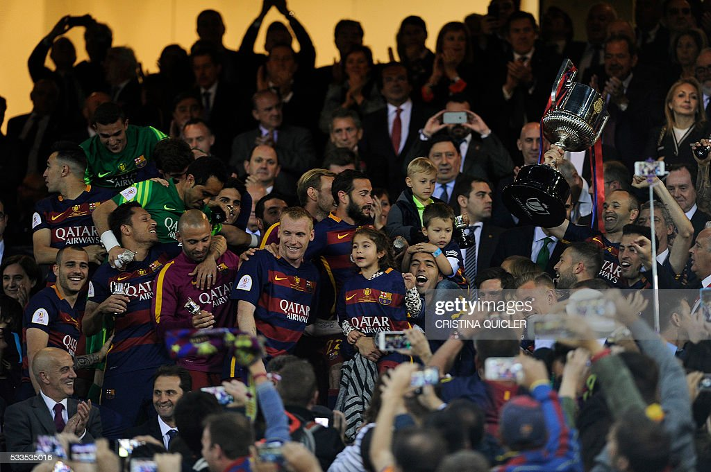 Barcelona's midfielder Andres Iniesta (R) holds the cup as he celebrates with teammates after winning the Spanish 'Copa del Rey' (King's Cup) final match FC Barcelona vs Sevilla FC at the Vicente Calderon stadium in Madrid on May 22, 2016. / AFP / CRISTINA