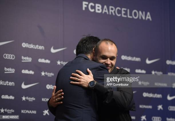 Barcelona's midfielder Andres Iniesta hugs the Catalan club's president Josep Maria Bartomeu after renewing his contract at the Camp Nou in Barcelona...