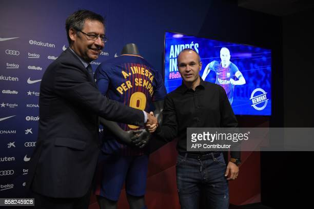 Barcelona's midfielder Andres Iniesta shakes hands with the Catalan club's president Josep Maria Bartomeu next to a special Barcelona FC jersey after...