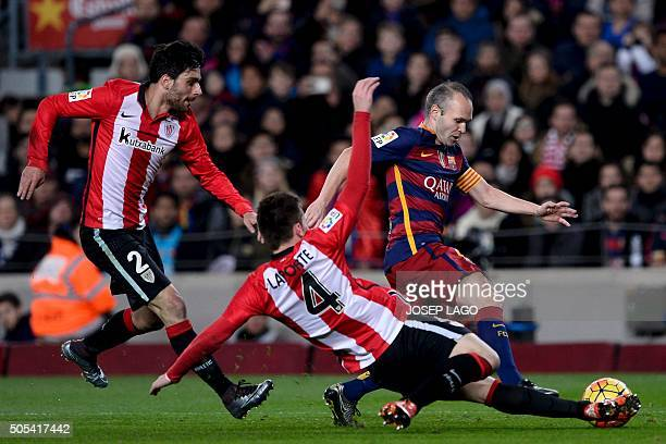Barcelona's midfielder Andres Iniesta vies with Athletic Bilbao's defender Eneko Boveda and Athletic Bilbao's French defender Aymeric Laporte during...