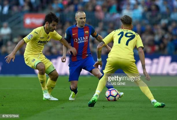 Barcelona's midfielder Andres Iniesta vies with Villarreal's midfielder Manu Trigueros and Villarreal's midfielder Samuel Castillejo during the...
