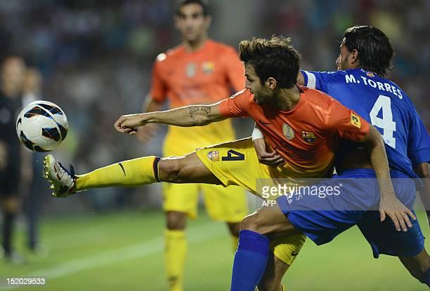 Barcelona's midfielder Cesc Fabregas vies with Getafe's defender Miguel Torres during the Spanish league football match Getafe vs Barcelona at...