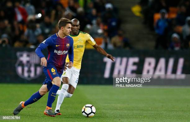 Barcelona's midfielder Denis Suarez vies with Mamelodi Sundown's defender Anele Ngcongca during their friendly football match Barcelona vs Sundowns...