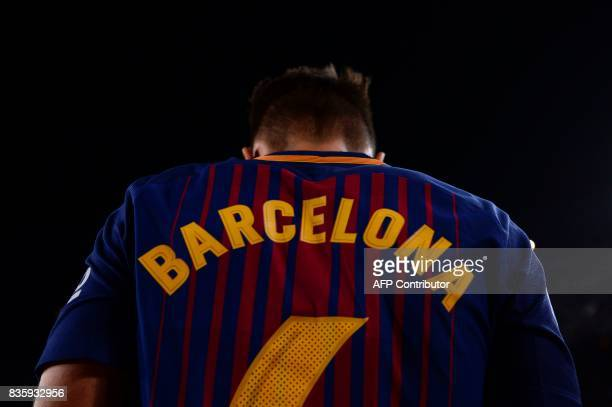 Barcelona's midfielder Denis Suarez wears a jersey reading 'Barcelona' instead of his name to pay tribute to the victims of the Barcelona and...