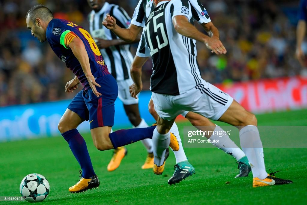 Barcelona's midfielder from Spain Andres Iniesta (L) vies with Juventus' defender from Italy Andrea Barzagli during the UEFA Champions League Group D football match FC Barcelona vs Juventus at the Camp Nou stadium in Barcelona on September 12, 2017. /