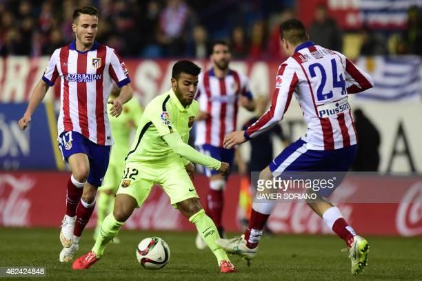 Barcelona's midfielder Rafinha vies with Atletico Madrid's midfielder Saul Niguez and Atletico Madrid's Uruguayan defender Jose Maria Gimenez during...