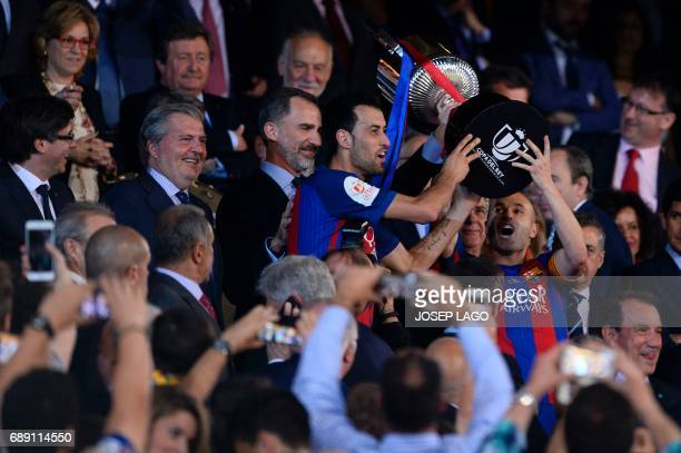 Barcelona's midfielder Sergio Busquets and Barcelona's midfielder Andres Iniesta hold up the cup after the team won the Spanish Copa del Rey final...