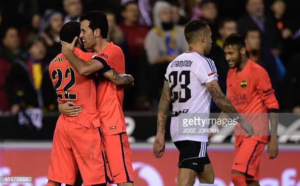 Barcelona's midfielder Sergio Busquets celebrates with Barcelona's Brazilian defender Dani Alves after scoring during the Spanish league football...