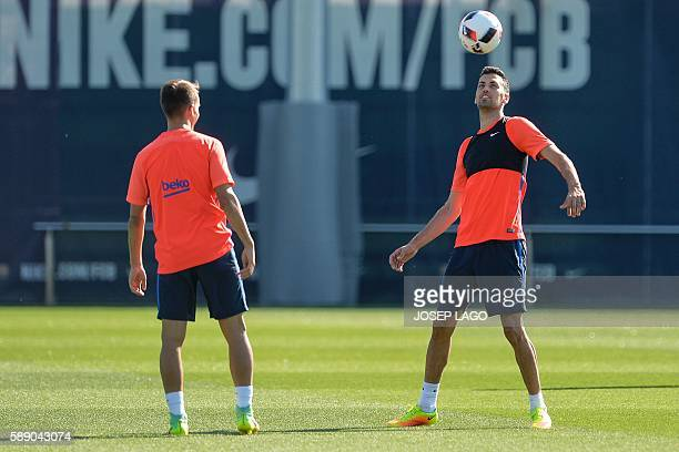 Barcelona's midfielder Sergio Busquets controls the ball next to Barcelona's midfielder Denis Suarez during a training session at the Sports Center...