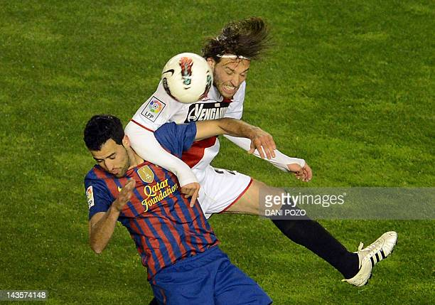 Barcelona's midfielder Sergio Busquets vies for the ball with Rayo Vallecano's midfielder Miguel Perez Cuesta during the Spanish League football...