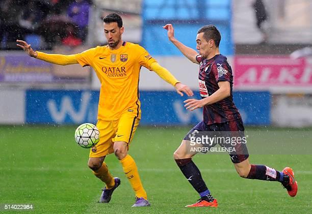 Barcelona's midfielder Sergio Busquets vies with Eibar's midfielder Gonzalo Escalante during the Spanish league football match SD Eibar vs FC...