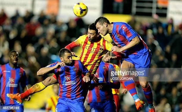 Barcelona's midfielder Sergio Busquets vies with Levante's defender David Navarro during the Spanish league football match Levante UD vs FC Barcelona...