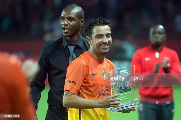 Barcelona's midfielder Spanish Xavi Hernandez holds the Paris' Trophy given by former team-mate Eric Abidal after defeating Paris Saint-Germain PSG...