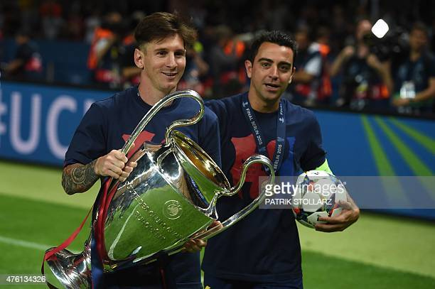 Barcelona's midfielder Xavi Hernandez and Barcelona's Argentinian forward Lionel Messi celebrate with the trophy after the UEFA Champions League...