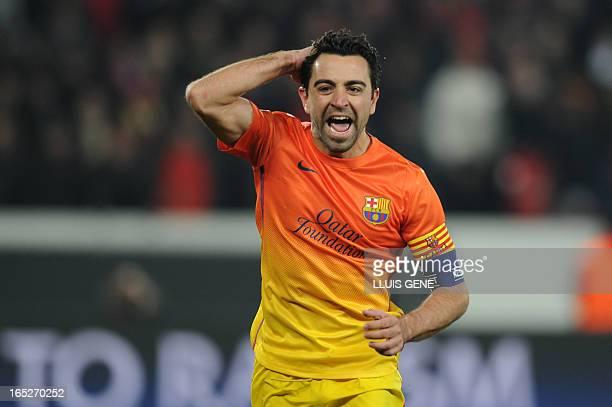 Barcelona's midfielder Xavi Hernandez celebrates after scoring a penalty during the Champions League quarter-final football match between Paris...
