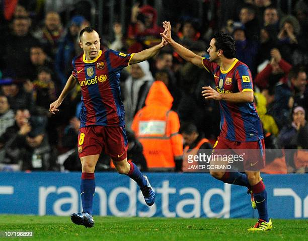 Barcelona's midfielder Xavi Hernandez celebrates his goal with teammate midfielder Andres Iniesta during the Spanish league 'clasico' football match...