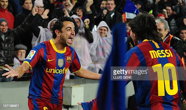Barcelona's midfielder Xavi Hernandez celebrates his goal with teammate Argentinian forward Lionel Messi during the Spanish league 'clasico' football...