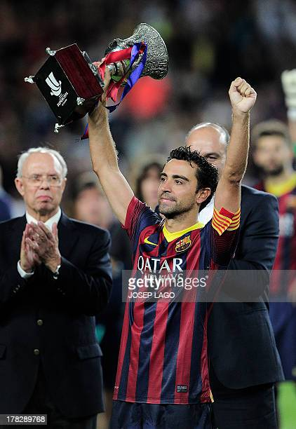 Barcelona's midfielder Xavi Hernandez celebrates their victory with the trophy at the end of the Spanish Super Cup second leg football match FC...
