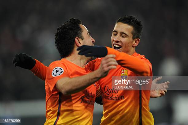 Barcelona's midfielder Xavi Hernandez celebrates with Barcelona's Chilean forward Alexis Sanchez after scoring against Paris Saint Germain during a...