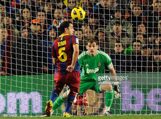 Barcelona's midfielder Xavi Hernandez controls the ball to score his team's first goal to Real Madrid's goalkeeper and captain Iker Casillas during...